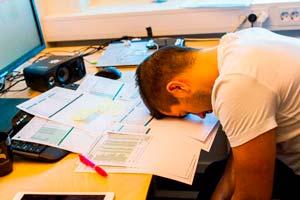 Mann sovner med arbeidspulten