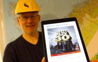 Vidar Berg-Hansen viser frem et nettbrett med NESO sitt 30-års jubileum.