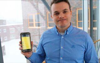 Mikal Johnsen holder en mobiltelefon med SmartDok